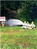 3 firefighters shooting water from hose