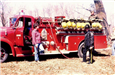 Two People Standing in Front of Red Fire Truck
