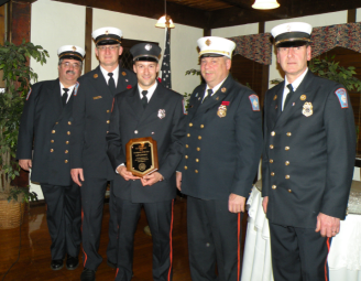 5 firefighters with one holding a plaque