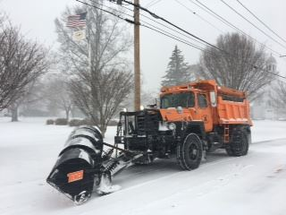 This is an image of an orange Mack truck snowplow.