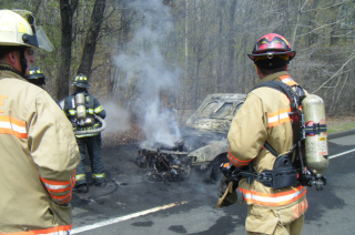 3 firefighters next to car covered in grey soot