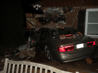 grey car crashed into brick house