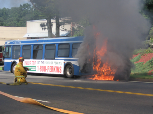 firefighter standing by a bus on fire